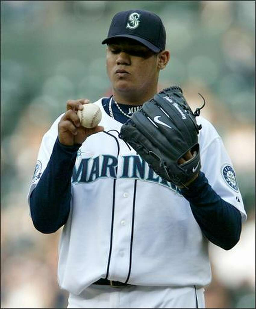 Seattle Mariners Felix Hernandez inspects the ball as he works through a rough start against the Boston Red Sox during first inning action at Safeco Field in Seattle Tuesday.