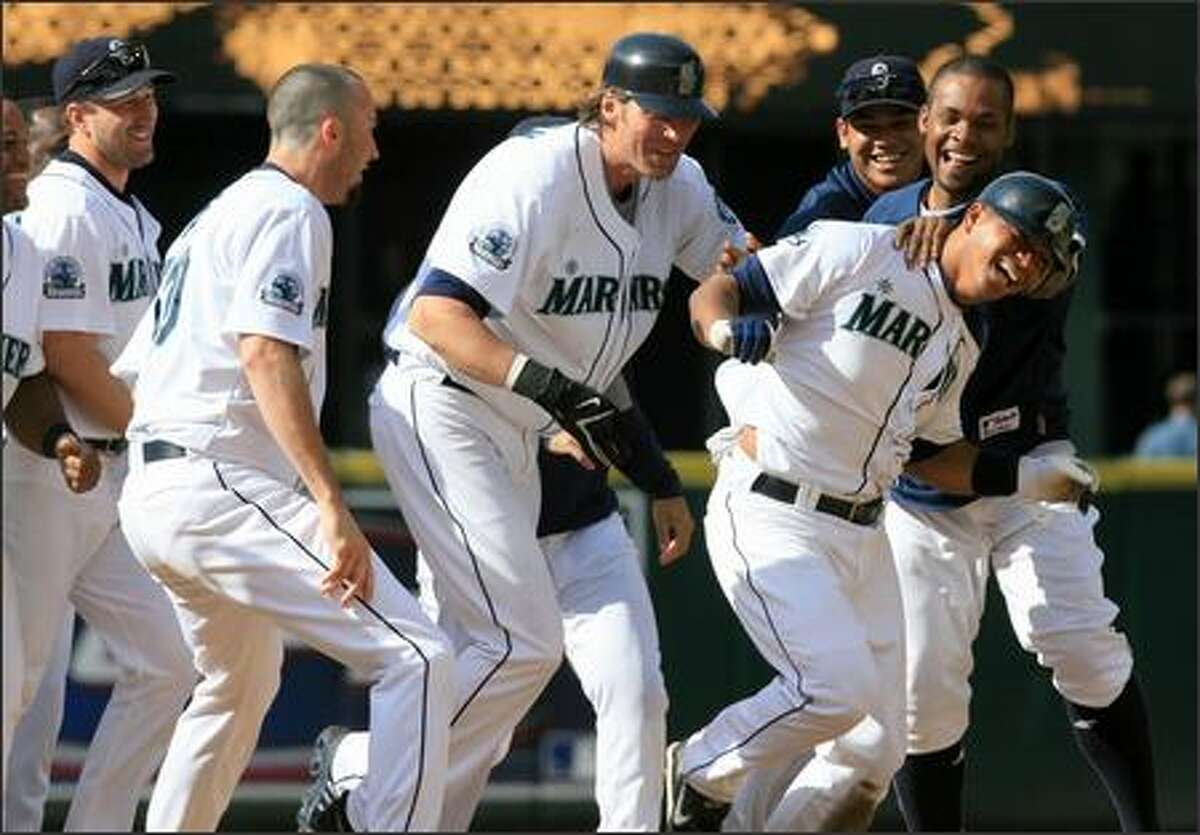 Jose Lopez, right, is mobbed by teammates after connecting for a game-winning double against Boston at Safeco Field on Wednesday. The Mariners won 2-1 in 11 innings to sweep a three-game series against the Red Sox, who have baseball's best record.