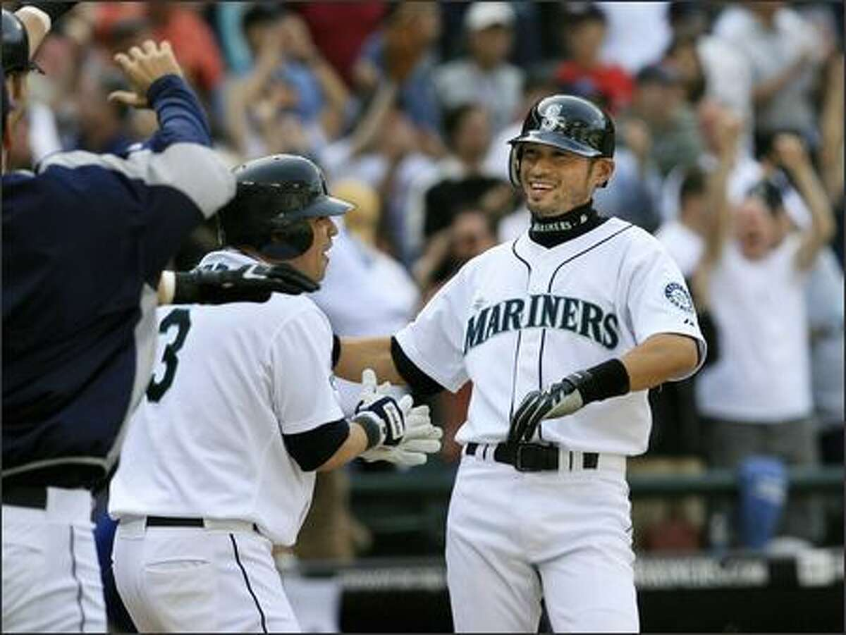 Ichiro Suzuki is congratulated by teammates, including Jose Vidro (3), after scoring the winning run on a double by Jose Lopez in the 11th inning.