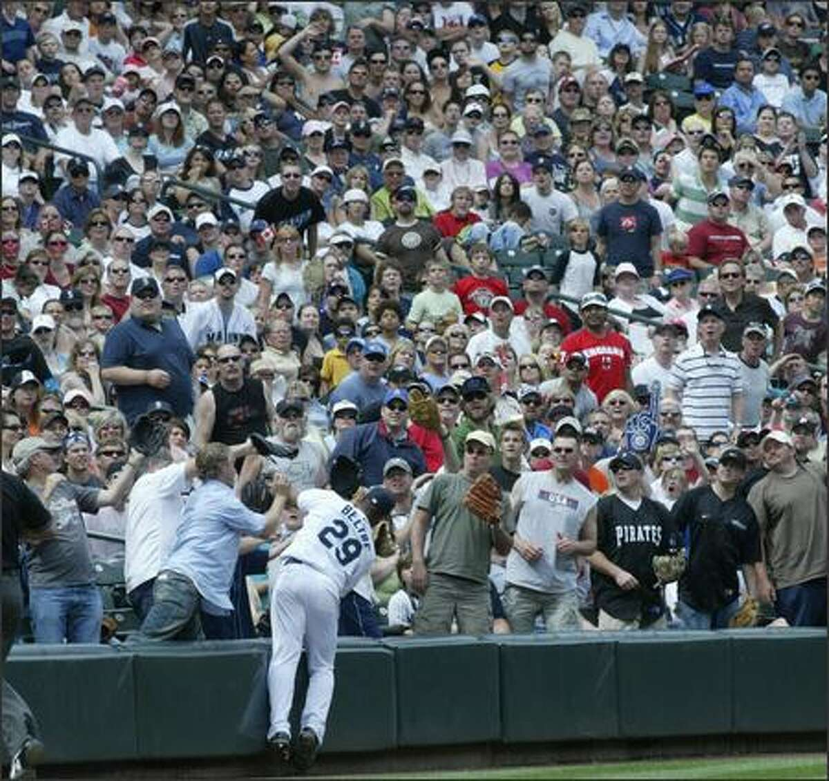 Mariners third baseman Adrian Beltre reaches into the crowd to catch a foul ball hit by Toronto's Matt Stairs for an out late in the game.