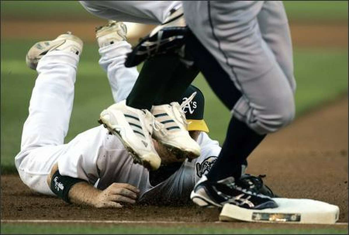 Oakland first baseman Dan Johnson dives to make the tag on Ichiro Suzuki (feet on base) as the feet of A's pitcher Chad Gaudin (white shoes) jump out of the way in the first inning. Suzuki was safe on the play. (AP Photo/Ben Margot)
