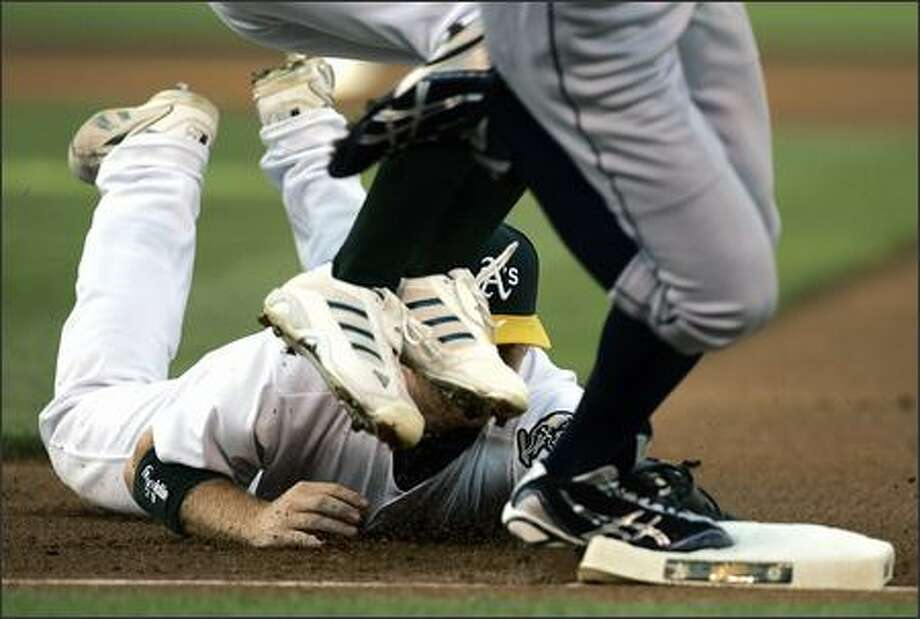 Oakland first baseman Dan Johnson dives to make the tag on Ichiro Suzuki (feet on base) as the feet of A's pitcher Chad Gaudin (white shoes) jump out of the way in the first inning. Suzuki was safe on the play. (AP Photo/Ben Margot) Photo: Associated Press / Associated Press
