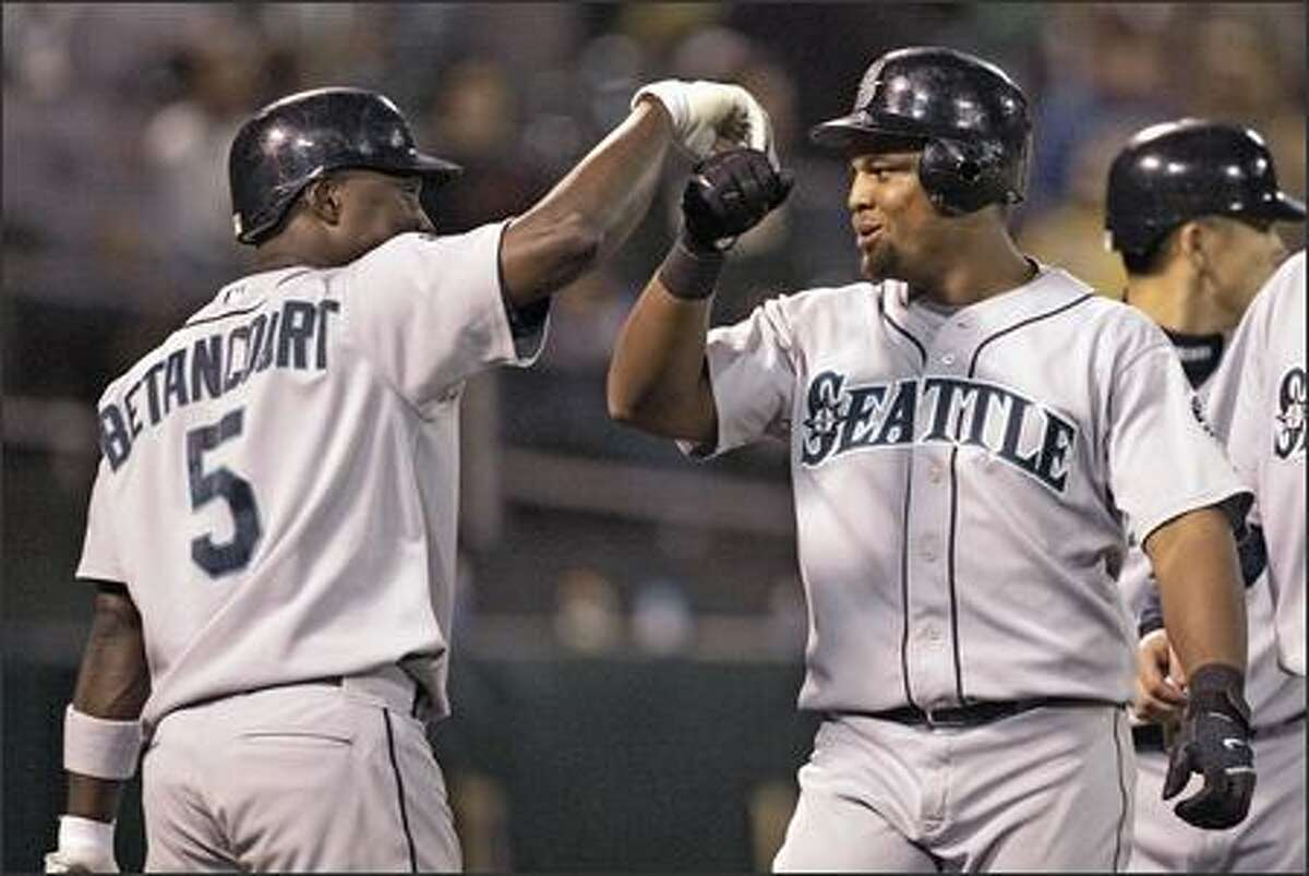 The M's Adrian Beltre, right, is congratulated by teammate Yuniesky Betancourt after hitting a two-run home run off the A's Joe Kennedy in the eighth inning of a baseball game Friday in Oakland. (AP Photo/Ben Margot)