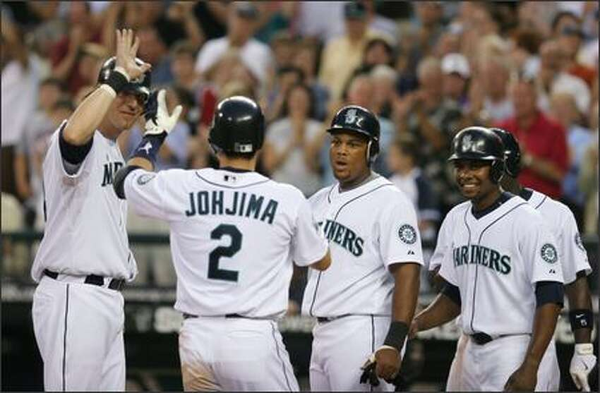 Kenji Johjima (2) is congratulated at home plate by teammates (from left) Richie Sexson, Adrian Beltre and Jose Guillen after Johjima hit a grand slam in the sixth inning for a 6-1 Seattle lead. (AP Photo/Kevin P. Casey)