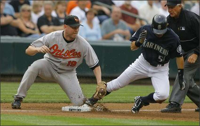 After hitting a double in the first inning Ichiro Suzuki #51 beats the tag of Aubrey Huff #19 as he steels 3rd base setting himself up to score as the Mariners go up against the Orioles Monday in the opener of a three game home stand at Safeco Field.