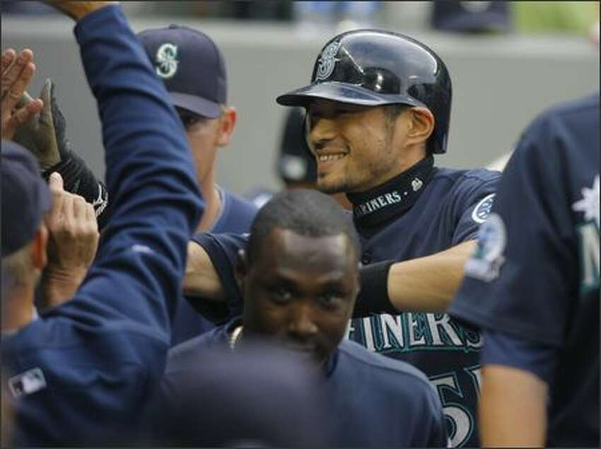 Seattle's Ichiro Suzuki is congratulated after scoring in the first inning against the Orioles Monday in the opener of a three game home stand at Safeco Field.