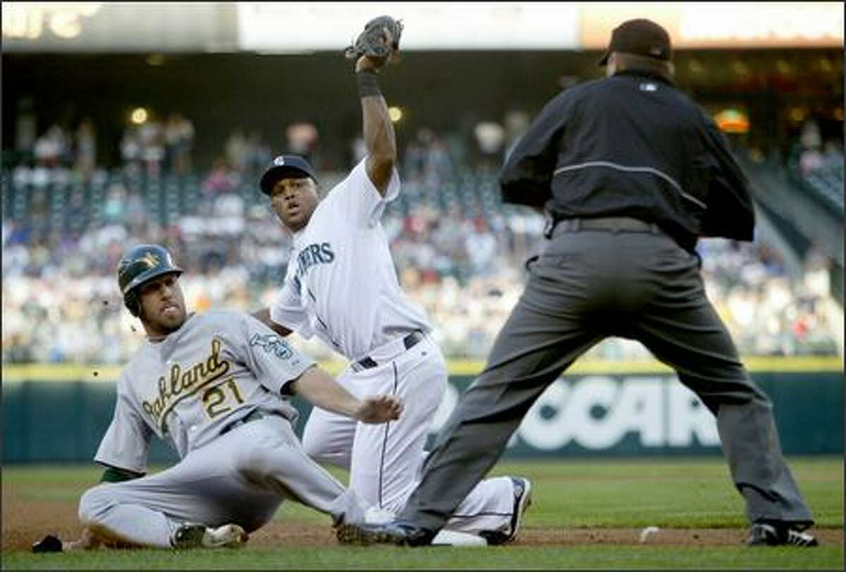 Seattle Mariner Adrian Beltre misses the tag on Oakland Athletics player Mark Kotsay at third base in the second inning on Thursday.