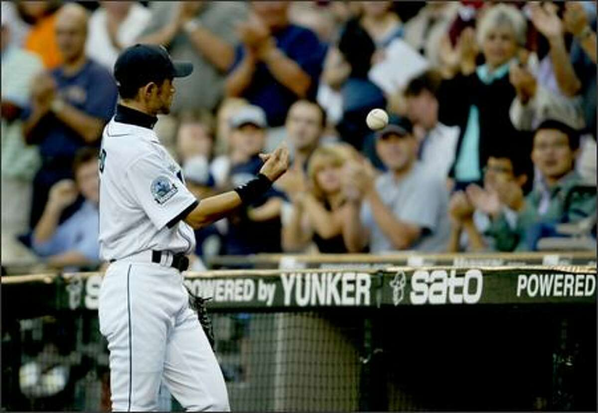 Seattle Mariners Ichiro Suzuki tosses the ball to a fan after a spectacular catch to end the top of the 4th inning off a fly ball to center Oakland Athletics Marco Scutaro on Thursday.