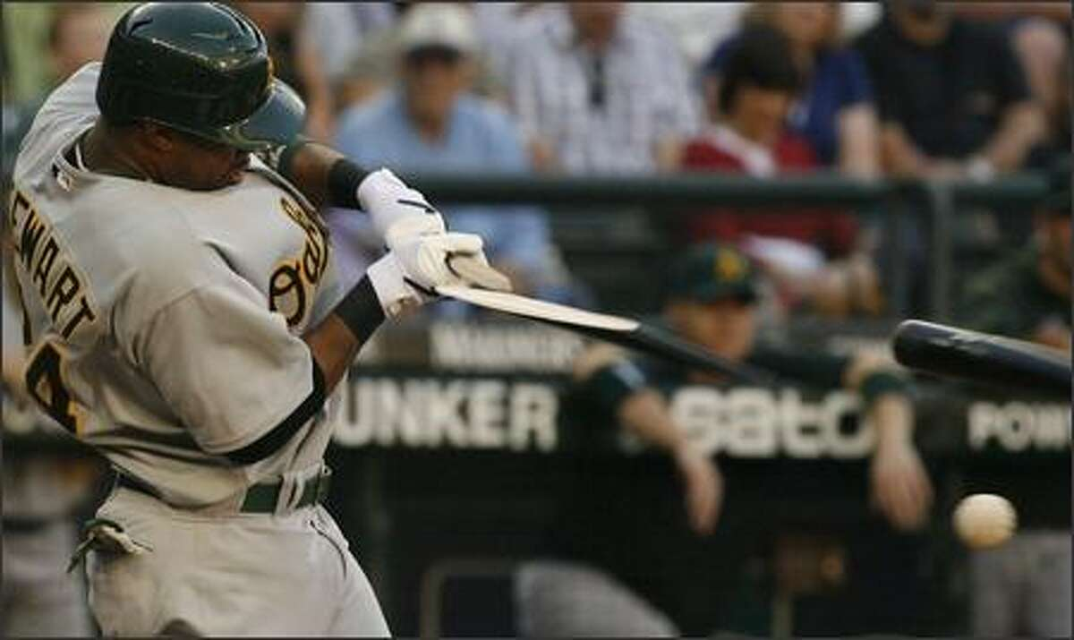 Oakland's Shannon Stewart shatters his bat into three pieces as he tries to hit a Felix Hernandez pitch in the first inning of the game between the Mariners and the Athletics on Friday.