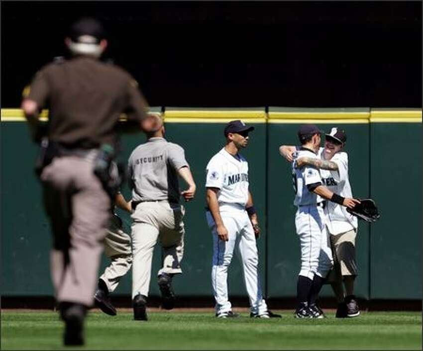 During a pitching change, Ichiro Suzuki gets hugged by a fan who ran onto the field and was taken into custody by security workers during the eighth inning of the Mariners' game against the Oakland Athletics. Seattle won 4-3. (AP Photo/Kevin P. Casey)