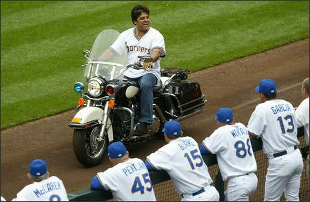 TV star Erik Estrada rides a police motorcycle past the Mariners dugout during Turn Back the Clock Day at Safeco Field before the game against the Oakland Athletics.