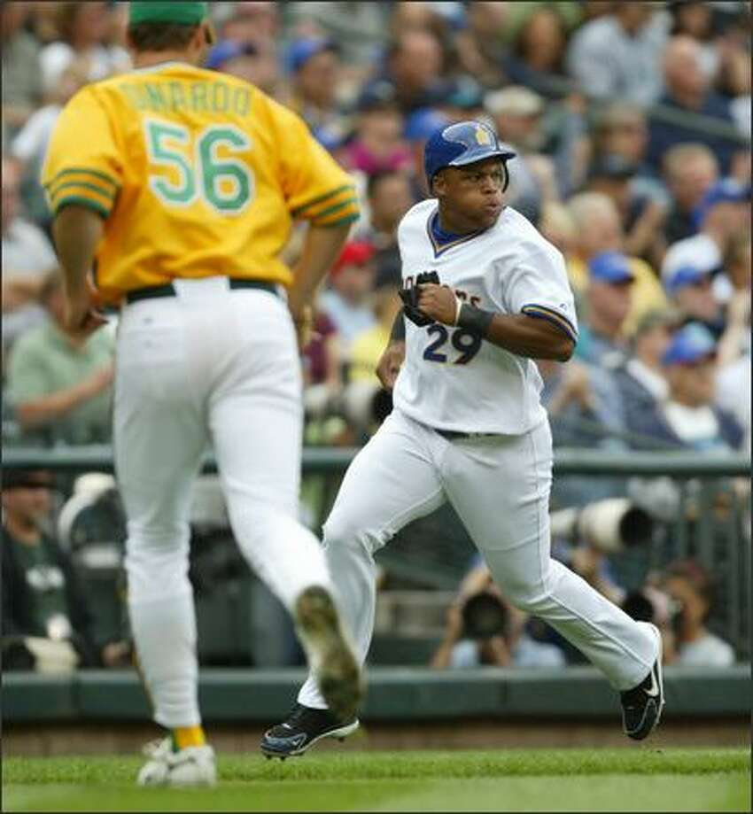 Seattle Mariners' Adrian Beltre scores on a Raul Ibanez single in the first inning as Oakland Athletics' pitcher Lenny DiNardo moves to cover home in the first inning.