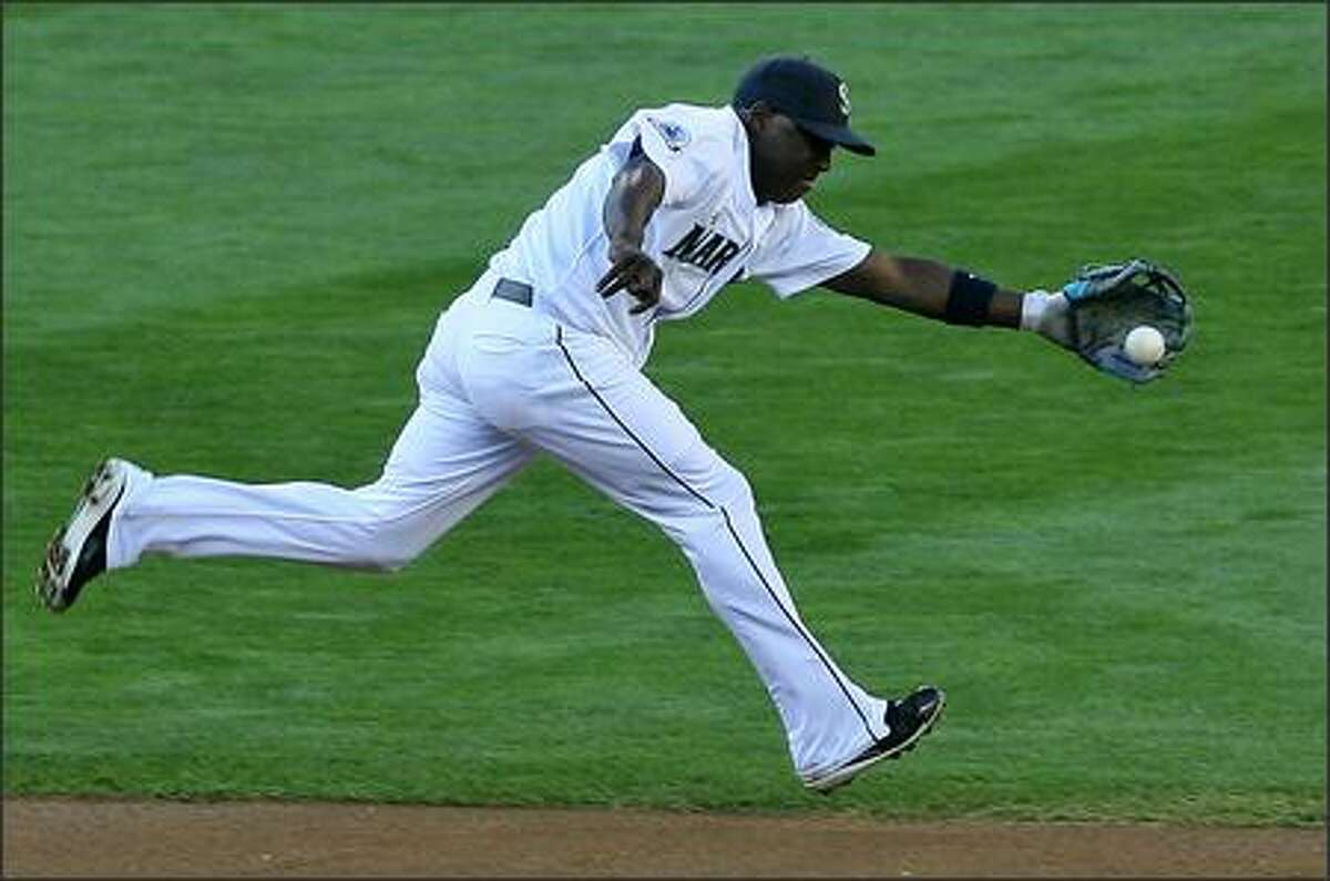 Seattle Mariners' Yuniesky Betancourt snags a ground ball off Los Angeles Angels' Chone Figgins during first inning action.