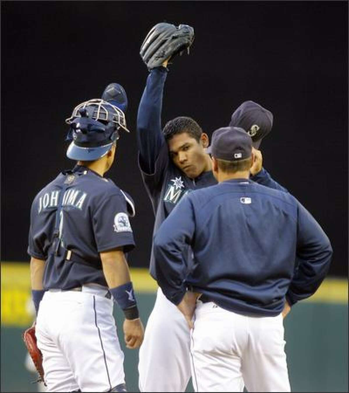 Seattle Mariner's pitcher Felix Hernandez stretches as he talks with catcher Kenji Johjima during a game against the Minnesota Twins at Safeco Field Monday, August 13, 2007.