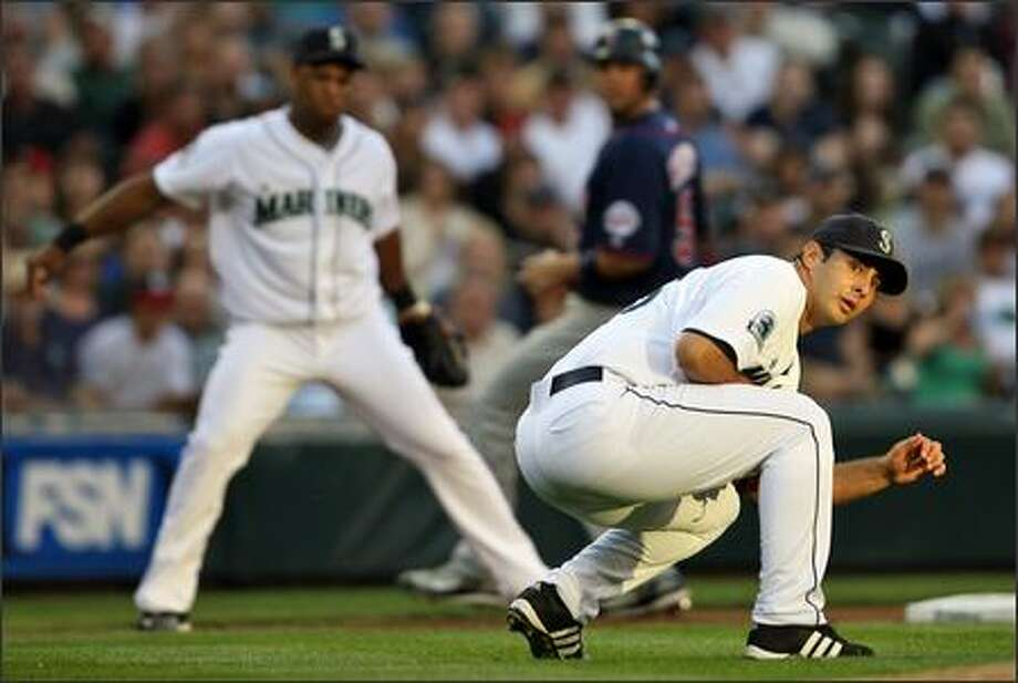 Mariners pitcher Horacio Ramirez ducks as he watches to see if Adrian Beltre's throw makes it to first in time to take out Minnesota's Nick Punto in the second inning. Photo: Mike Urban, Seattle Post-Intelligencer / Seattle Post-Intelligencer