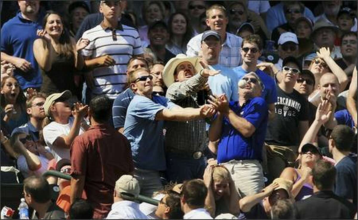 Fans battle for a foul ball hit by Seattle's Raul Ibanez. With this home game, the 62nd of the season, Safeco Field attendance surpassed 2 million for the 2007 season.