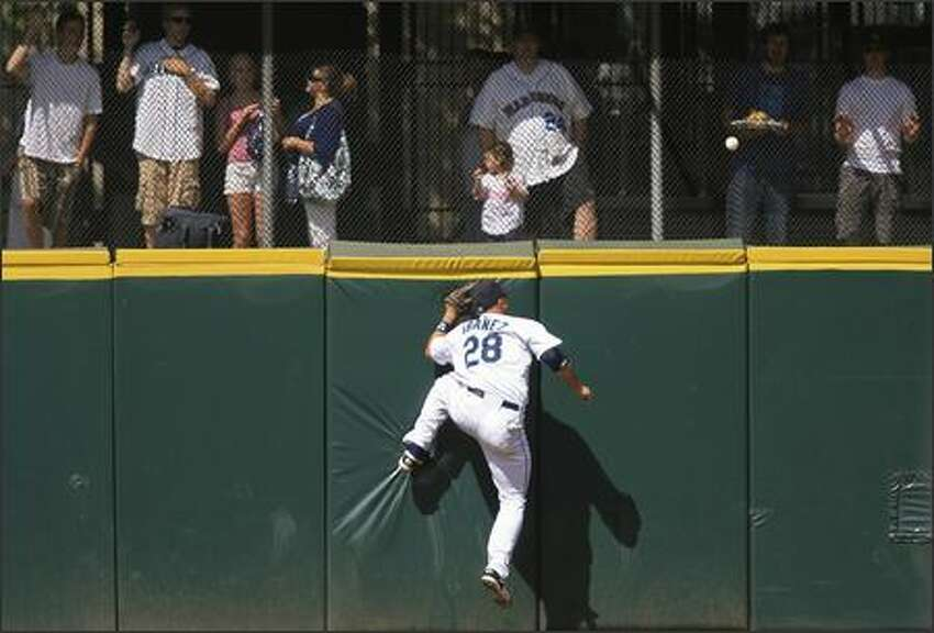 Mariners left fielder Raul Ibanez tries in vain to catch a home run hit by Minnesota's Rondell White in the fifth inning.