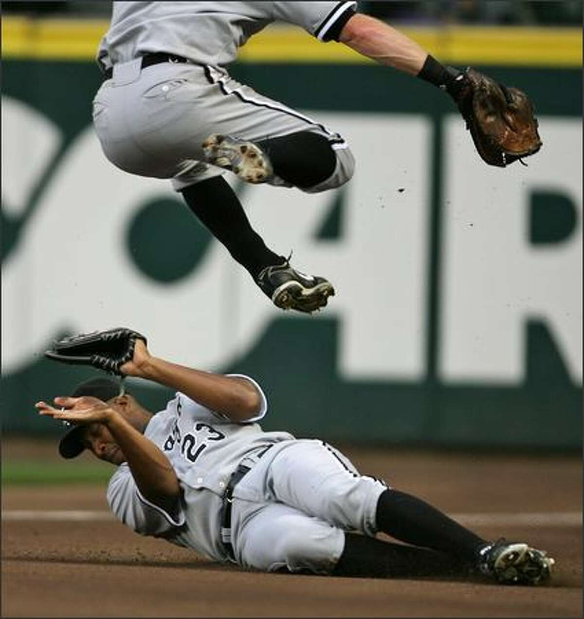 Chicago White Sox Jermaine Dye (23) shields himself as teammate Darin Erstad (17) leaps overhead as they both chase a foul ball hit by Seattle Mariners Yuniesky Betancourt into the right field warning track during second inning action at Safeco Field in Seattle, Wash., Friday August 17, 2007.