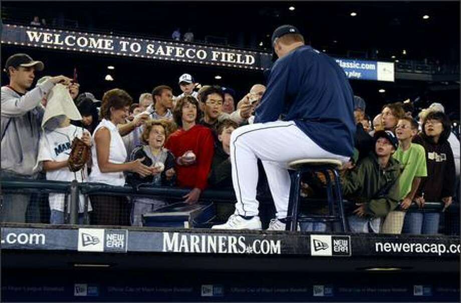 Sitting atop the Mariners dugout, closer J.J. Putz signs autographs for fans prior to the game against the Chicago White Sox at Safeco Field. Photo: Andy Rogers, Seattle Post-Intelligencer / Seattle Post-Intelligencer