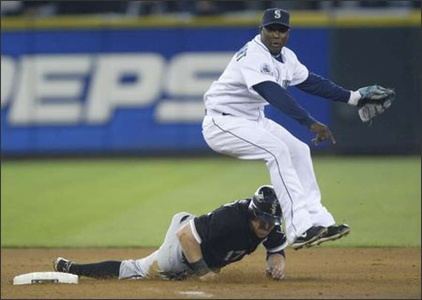 Yuniesky Betancourt tries to avoid the hard slide of Darin Erstad while turning a double play in the first inning.