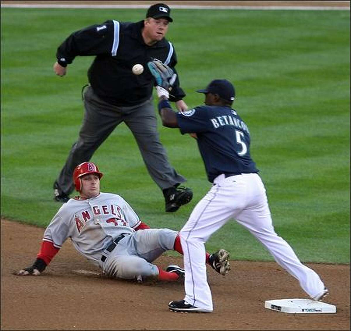 Seattle Mariners Yuniesky Betancourt takes Los Angeles Angels Reggie Willits out at second and turns the double play during for the final out of the first inning at Safeco Field in Seattle, Wash., Monday August 27, 2007. Second base umpire Bruce Dreckman observes the play.