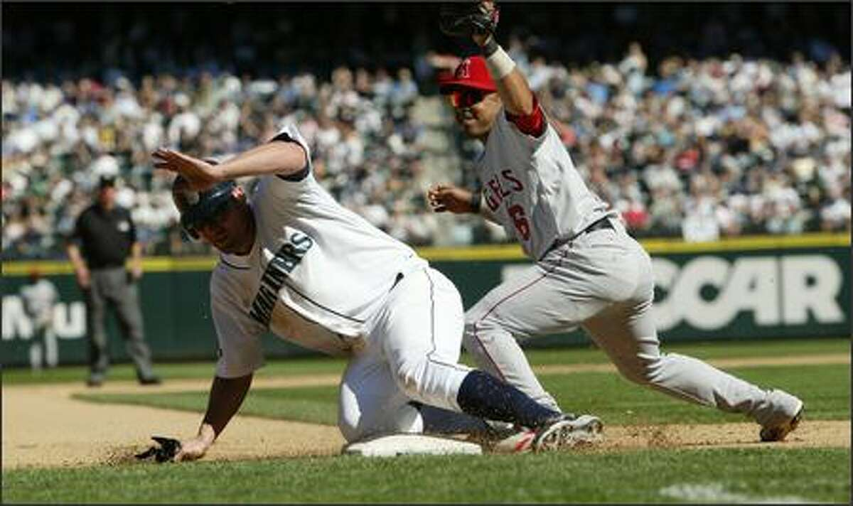 Seattle Mariner Ben Broussard is called out at third on a tag by Los Angeles Angels player Maicer Izturis in the 7th inning on Wednesday, August 29, 2007 at Safeco Field in Seattle. Mariners coach John McLaren came onto the field to protest the call.