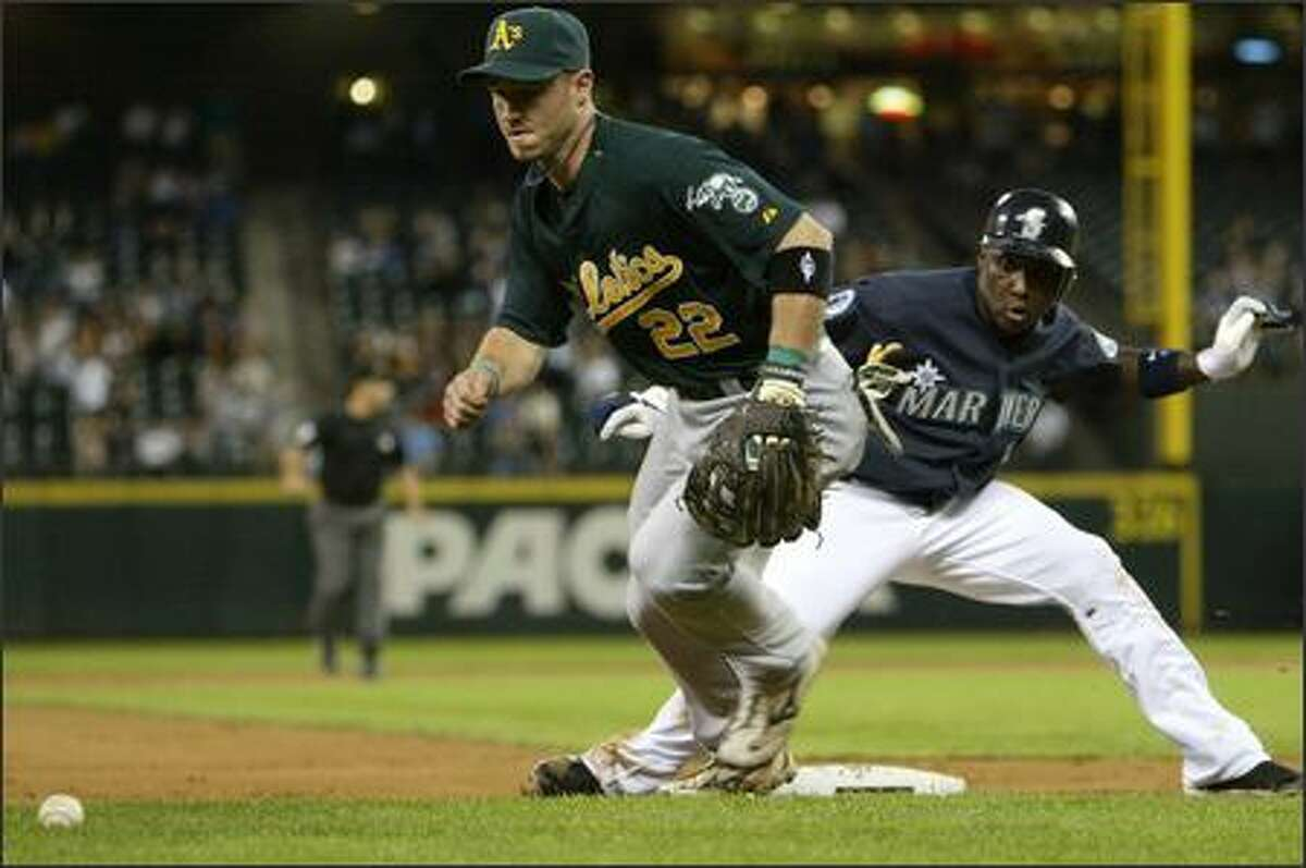 Seattle Mariners player Yuniesky Betancourt is tempted to run to third after Oakland Athletics third baseman Jack Hannahan chases a loose ball during the 7th inning.