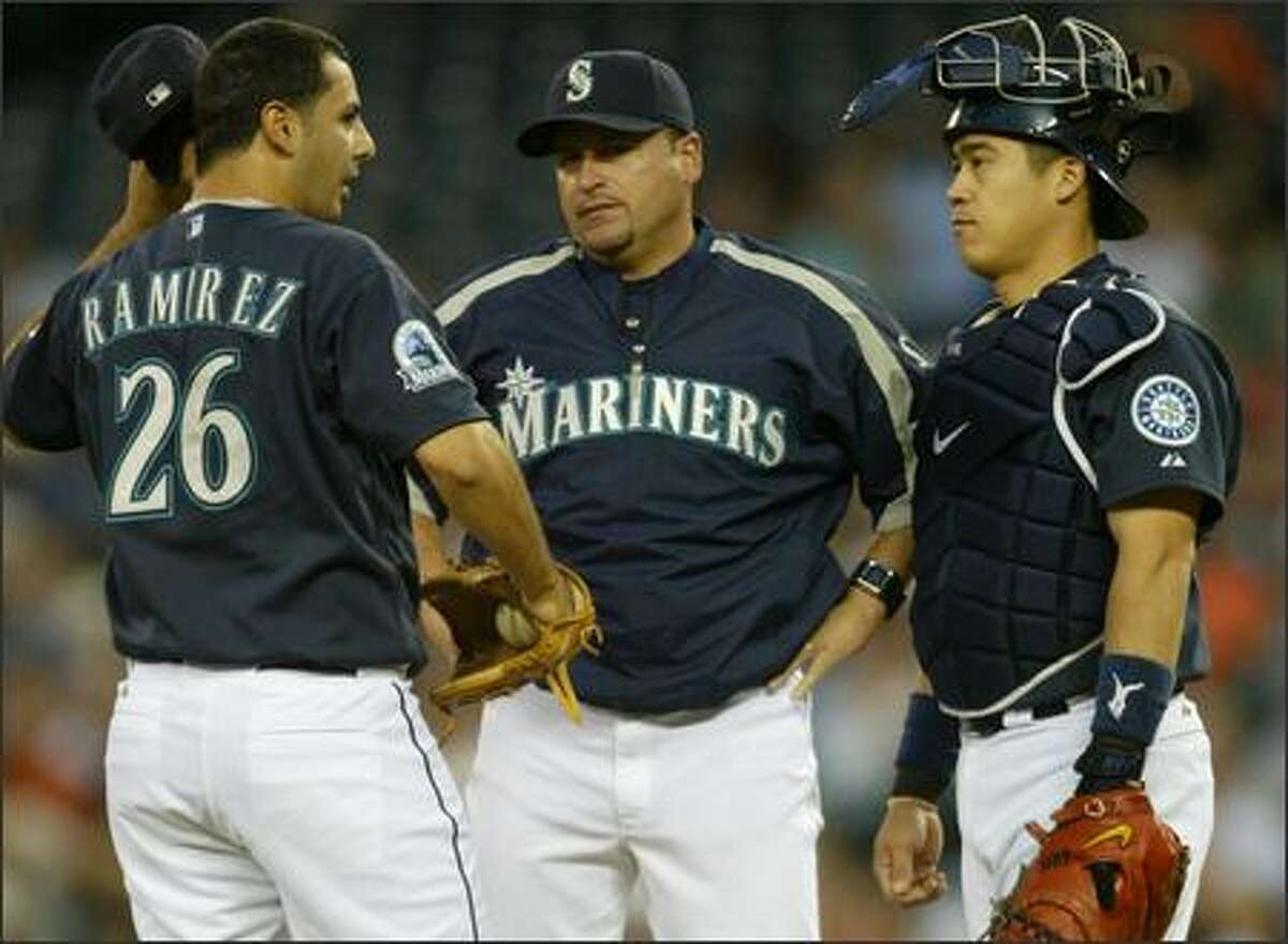 Seattle Mariners pitcher Horacio Ramirez is met at the plate by pitching coach Rafael Chaves and catcher Kenji Johjima after the second inning against the Oakland Athletics.