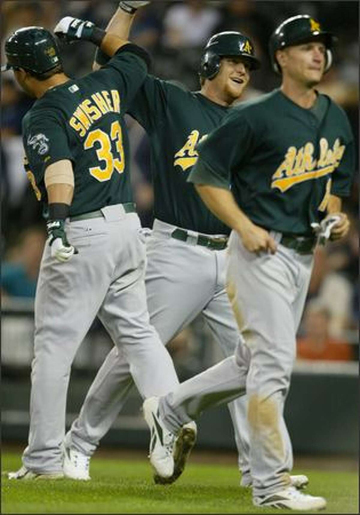 Oakland Athletics Dan Johnson, center, is greeted at home plate by teammate Nick Swisher after a grand slam during the 8th inning at Safeco Field.