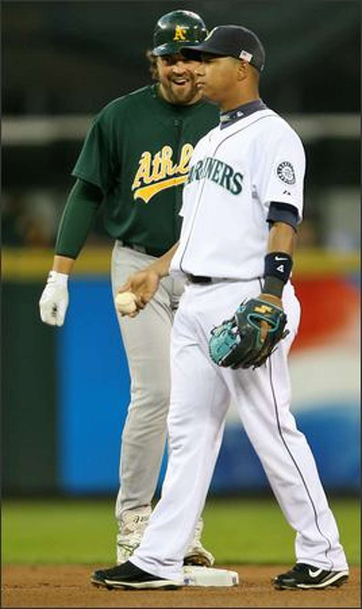 Oakland Athletics Mike Piazza smiles at an unimpressed Jose Lopez after hitting a double to center field during second inning action at Safeco Field.