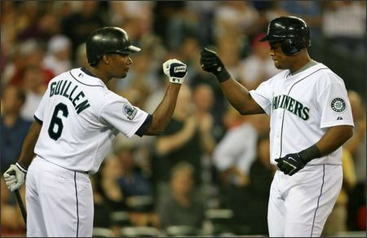 Seattle Mariners Adrian Beltre knocks knuckles with Jose Guillen after hitting a solo home run against the Oakland Athletics during third inning action at Safeco Field.