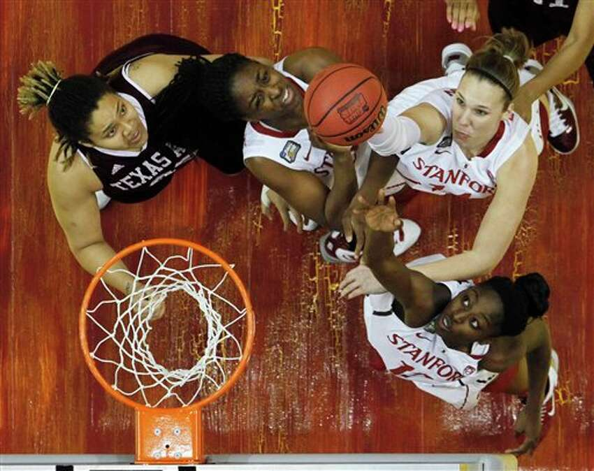 Stanford players Kayla Pedersen, top right, Chiney Ogwumike, bottom right, Nnemkadi Ogwumike, center, and Texas A&M's Danielle Adams, left, battle for a rebound in the first half of a women's NCAA Final Four semifinal college basketball game in Indianapolis, Sunday, April 3, 2011.