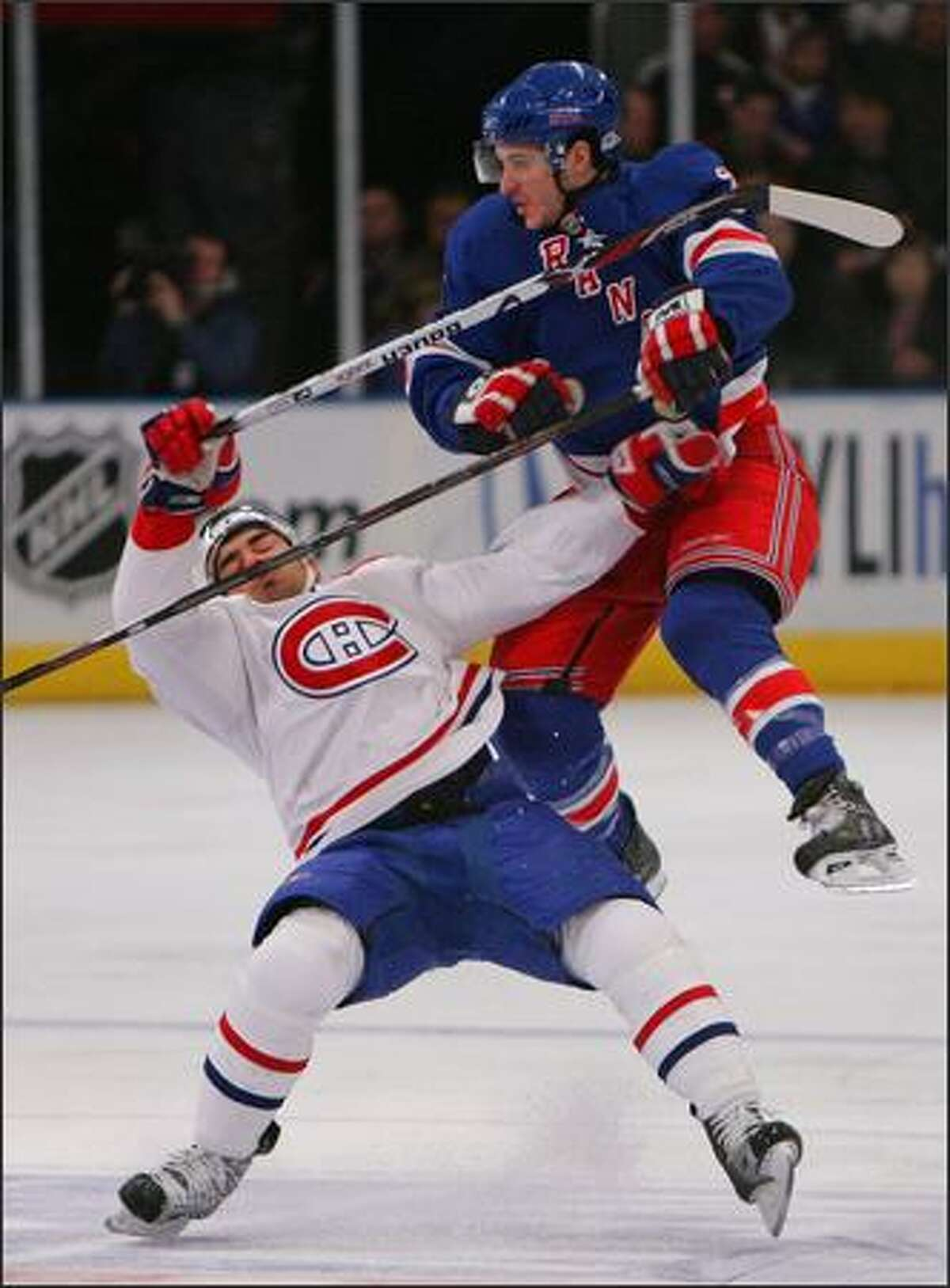 Francis Bouillon #51 of the Montreal Canadiens is hit by Ryan Callahan #24 of the New York Rangers at Madison Square Garden in New York City. Photo by Bruce Bennett/Getty Images