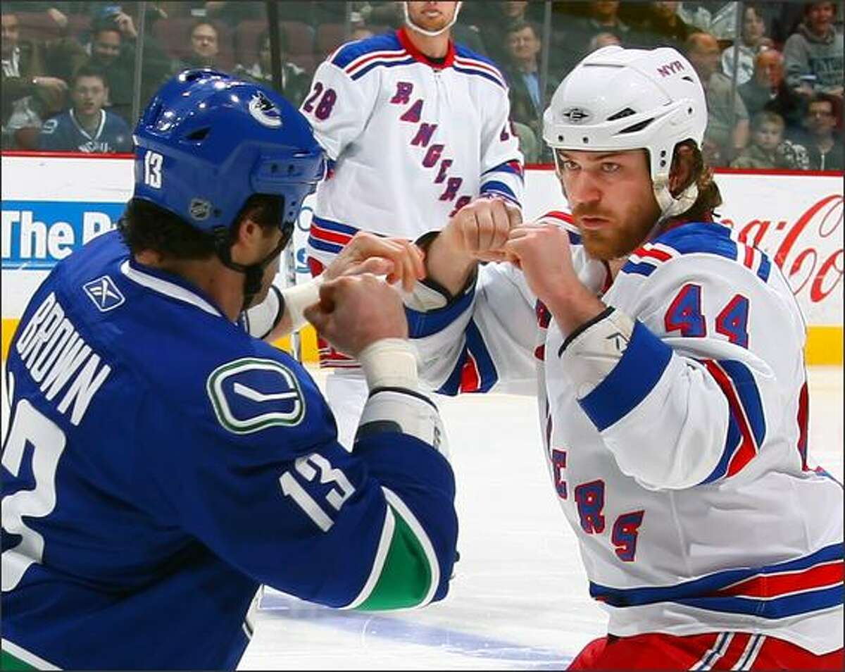 Mike Brown #13 of the Vancouver Canucks and Ryan Holweg #44 of the New York Rangers put up their dukes as the two fight during their game at General Motors Place in Vancouver, British Columbia, Canada. The Canucks shutout the Rangers 3-0. Photo by Jeff Vinnick/NHLI via Getty Images
