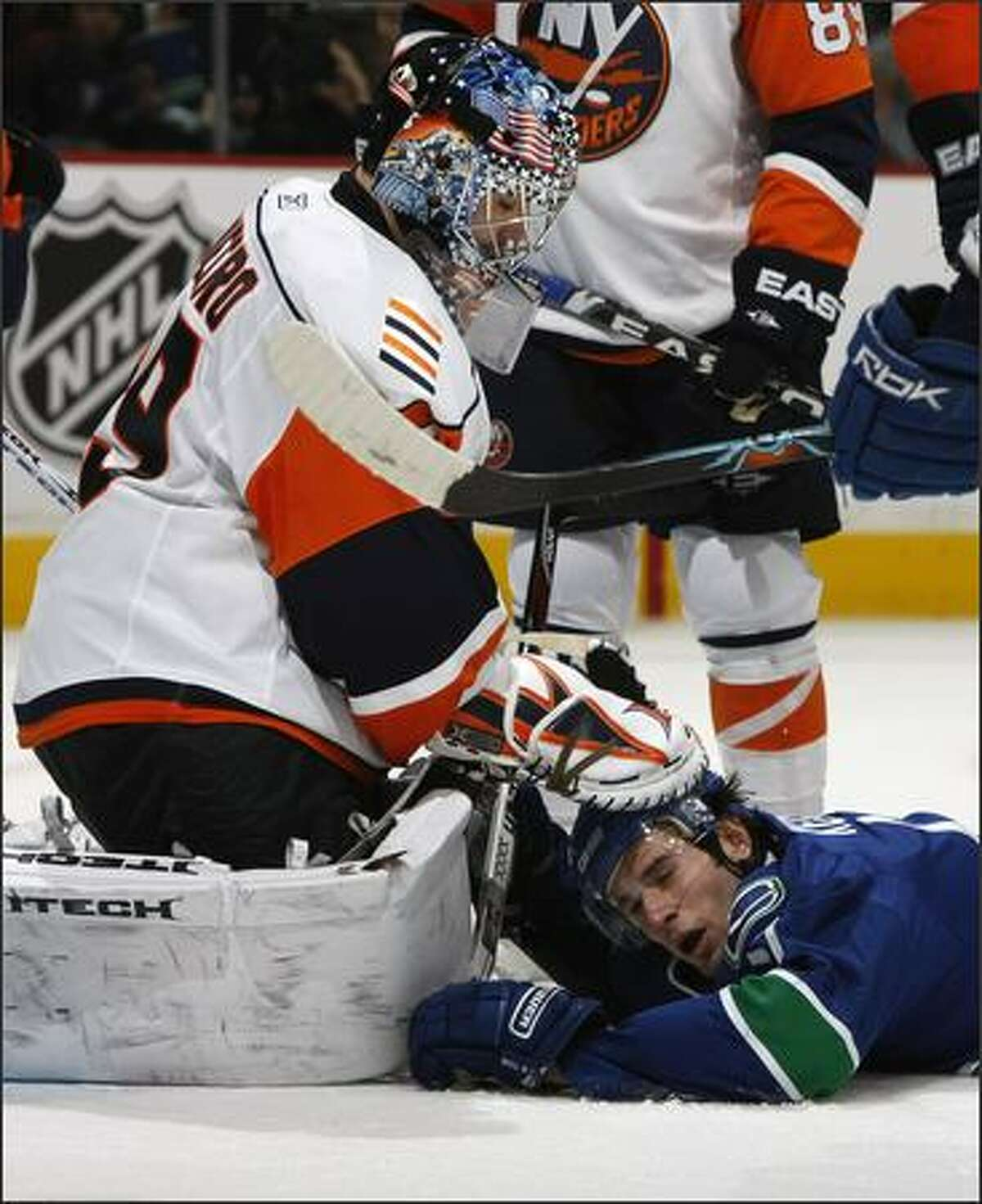 Goaltender Rick DiPietro #39 of the New York Islanders hits Ryan Kesler #17 of the Vancouver Canucks over the head with his glove during their game at General Motors Place in Vancouver, British Columbia, Canada. Photo by Jeff Vinnick/NHLI via Getty Images