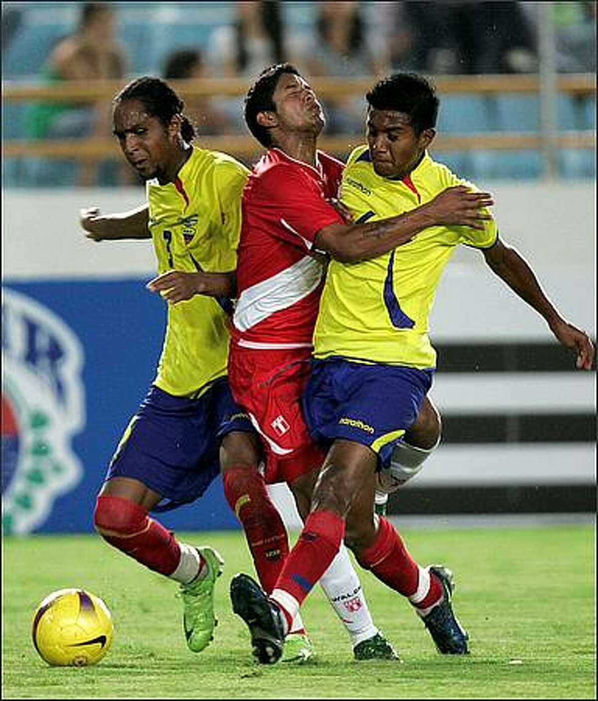 Ecuador's Deison Mendez, left, and Hamilton Shasi, right, push Peru's Reimond Manco during their under-20 South American soccer championship game in Maturin, Venezuela, Monday, Jan 19, 2009. (AP Photo/Fernando Llano)