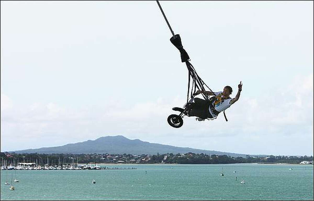 Steve Mini rides a motorbike off the bungy tower as the Crusty Demons bungee jump off Auckland Harbour Bridge in Auckland, New Zealand.