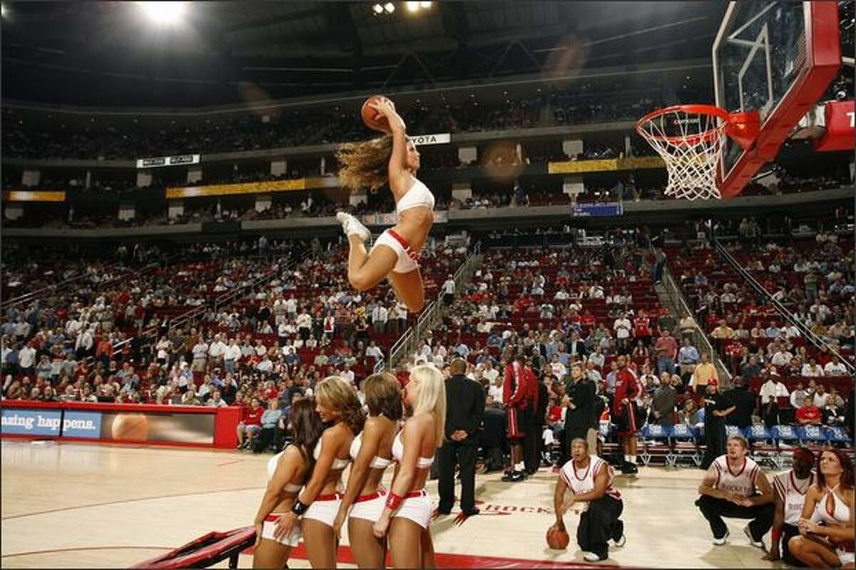 A Power Dancer of the Houston Rockets dunks the ball over four fellow dancers at the Toyota Center in Houston, Texas. Photo by Bill Baptist/NBAE via Getty Images