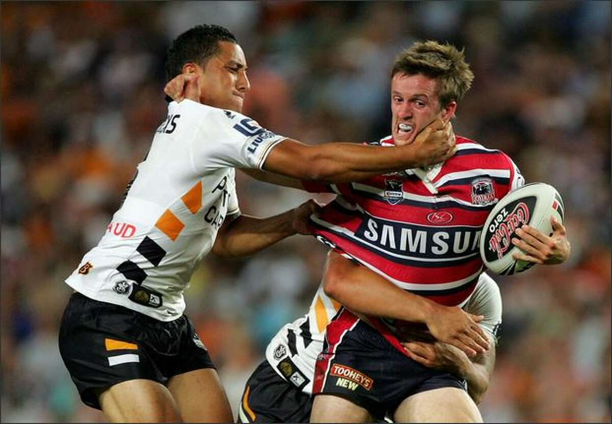Benji Marshall of the Wests Tigers tries to tackle Shaun Foley of the Roosters during the NRL Foundation Cup match between the Sydney Roosters and the Wests Tigers at the Sydney Football Stadium in Sydney, Australia. Photo by Ezra Shaw/Getty Images