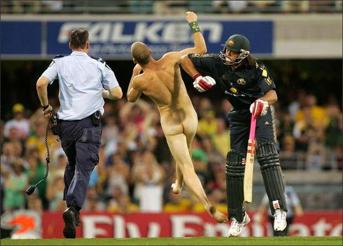 Andrew Symonds of Australia knocks over a streaker who ran onto the field during the Commonwealth Bank Series One Day International second final match between Australia and India at the Gabba in Brisbane, Australia. Photo by Ezra Shaw/Getty Images
