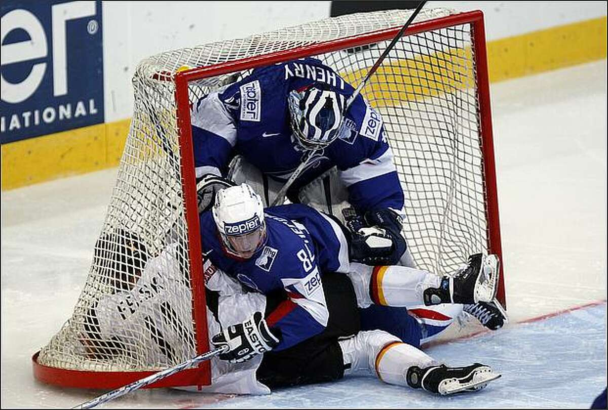 Germany's Sven Felski, left, ends up in the net with France's Kevin Hecquefeuille, center, and goaltender Fabrice Lhenry, right, during their IIHF World Hockey Championship game April 28 in Bern, Switzerland.