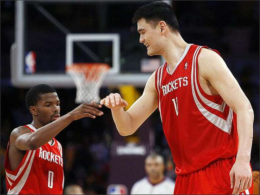 Houston Rockets center Yao Ming slaps hands with teammate Aaron Brooks after defeating the Los Angeles Lakers in Game 1 of their NBA Western Conference semifinal playoff game May 4 in Los Angeles.