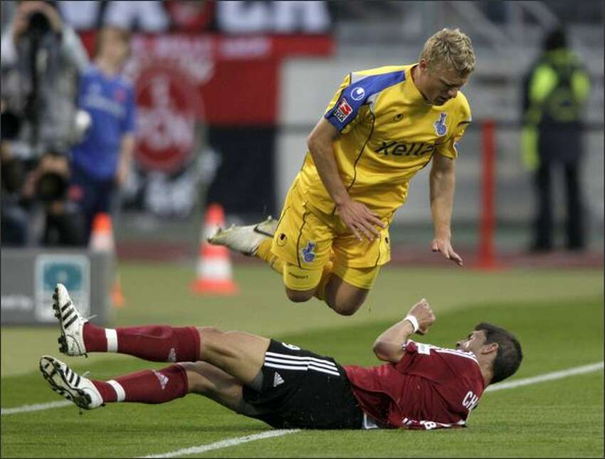 Tobias Willi of Duisburg is jumping over Angelos Charisteas of Nuernberg during the Bundesliga match between 1.FC Nuernberg and MSV Duisburg at the EasyCredit stadium in Nuremberg, Germany. (Photo by Thomas Langer/Bongarts/Getty Images)