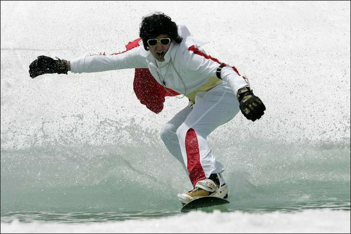 Elvis impersonator Todd Wells, 38, of Bend, Oregon glides across an icy pond on his snowboard Sunday May 18, 2008 5 at the Pond Skimming Championships in Mount Bachelor, Ore. Wells was one of 75 participants in the event, which takes place each year on the final day of the season for skiers and snowboarders. (AP Photo/The Bulletin,Andy Tullis)