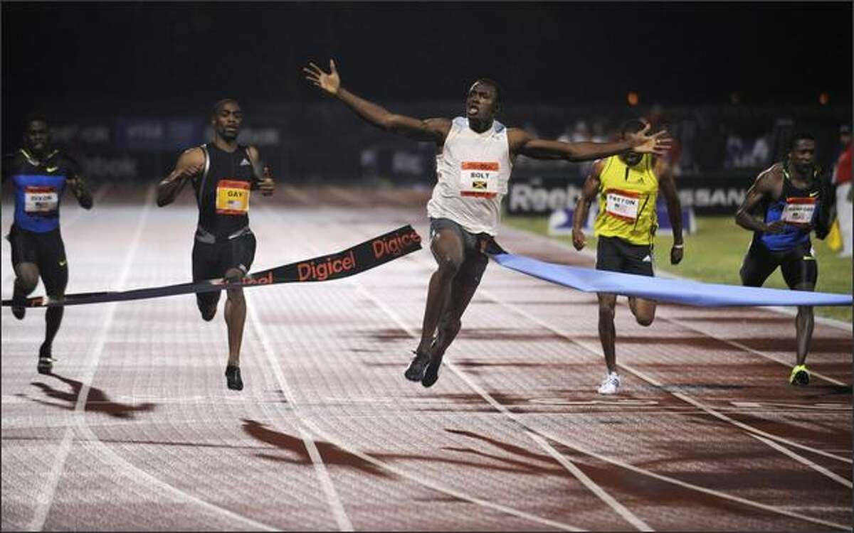 Jamaica's Usain Bolt, center, breaks the tape for a world record time of 9.72 seconds in the men's 100 meter sprint at the Reebok Grand Prix athletics meet Saturday night at Icahn Stadium in New York. (AP Photo/Bill Kostroun)