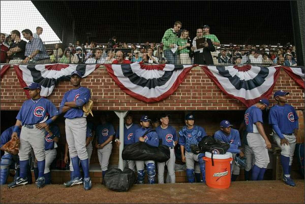 Chicago Cubs players stand in their dugout during a thunder storm at the Hall of Fame Game at Doubleday Field in Cooperstown, N.Y. The Cubs game against the San Diego Padres was cancelled. It was the final Hall of Fame game. (AP Photo/Mike Groll)