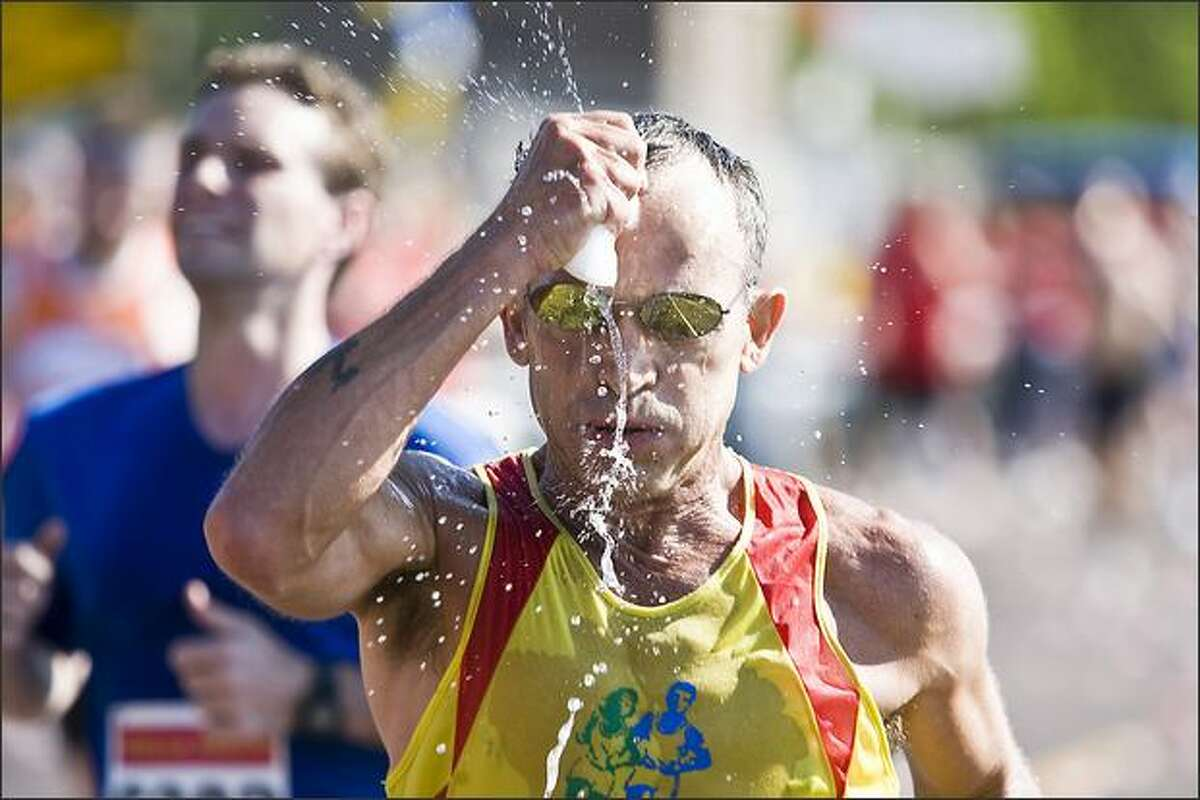 Bart Yasso of Emmaus, Pa., squeezes water out of a sponge at the 13-mile mark of the Grandma's Marathon in Duluth, Minn. (AP Photo/Duluth News Tribune, Clint Austin)