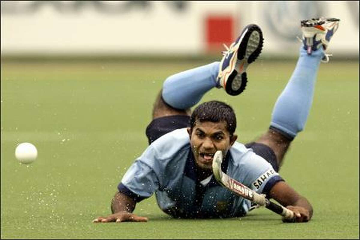 India's Sunil Yadav slides on the pitch during the men's field hockey Champions Challenge match between India and Japan in Boom, Belgium, Saturday, June 30, 2007. (AP Photo/Yves Logghe)