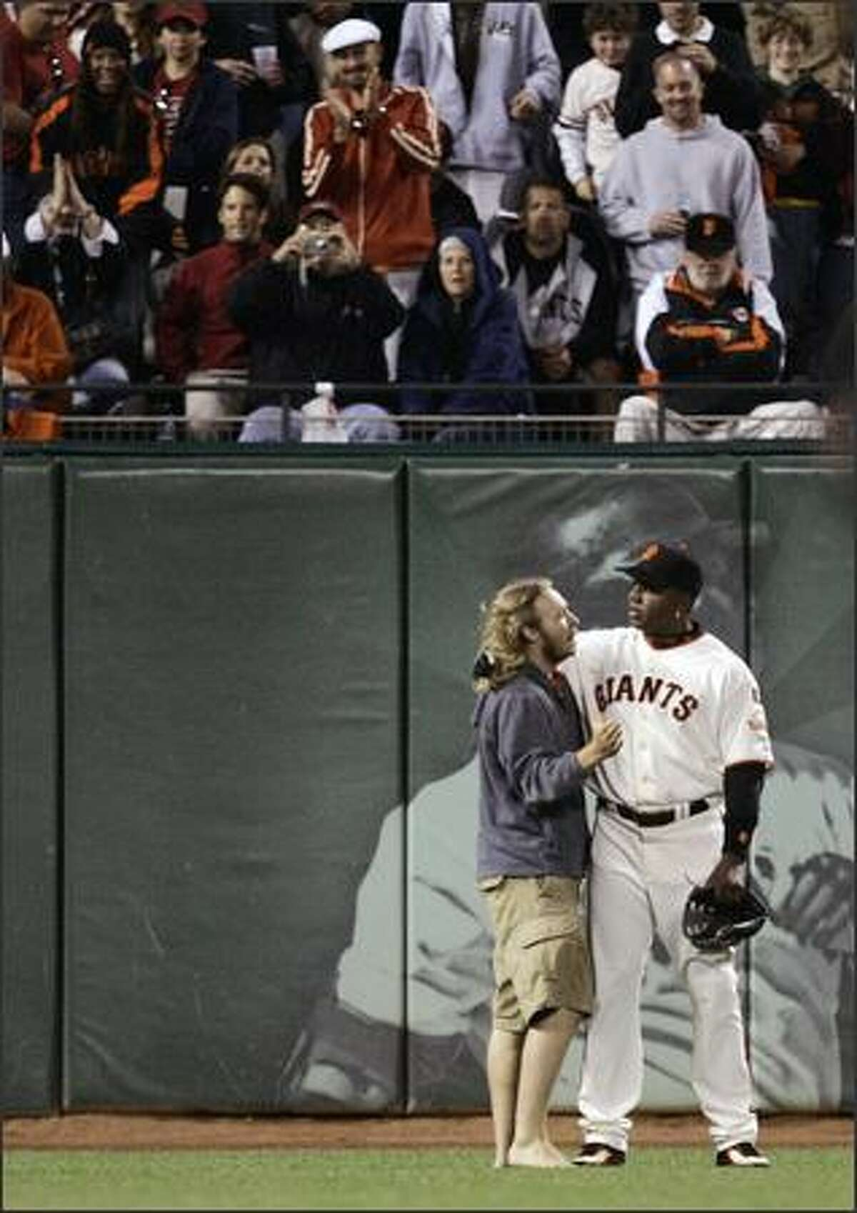 San Francisco Giants' Barry Bonds, right, puts his arm around a fan that walked out to greet him in left field during the seventh inning of a baseball game against the Arizona Diamondbacks, Friday, June 29, 2007, in San Francisco. (AP Photo/Ben Margot)