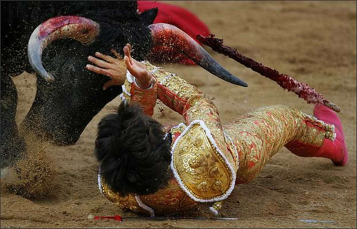 French matador Sebastian Castella is gored by a Fuente Ymbro's ranch bull during a bullfight in Pamplona, northern Spain, at the San Fermin festivities on The fiestas 'Los San Fermines' held since 1591, which attract tens of thousands of foreign visitors each year for nine days of revelry, morning bull-runs and afternoon bullfights. The San Fermin festival gained worldwide fame in Ernest Hemingway's 1926 novel 'The Sun Also Rises.' (AP Photo/Daniel Ochoa de Olza)